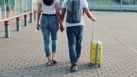 Det lyckliga barnparet går med bagage nära flygplatsen eller järnvägsstationen Begreppet av loppet, semestrar, ferier lager videofilmer