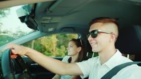 Det lyckliga barnparet reser med bilen En man kör en bil, frun sitter närliggande positiva sinnesrörelser stock video