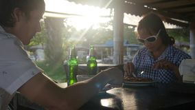 Det lyckliga barnparet som äter mål, dricker öl i det friakafé på sommardag royaltyfri bild