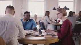 Det lyckliga blandade etnicitetlaget av frilans- affärsfolk arbetar tillsammans vid tabellen i coworking kontor för modern vind stock video