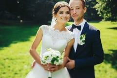 Det lyckliga bröllopparet poserar i trädgården Royaltyfri Fotografi