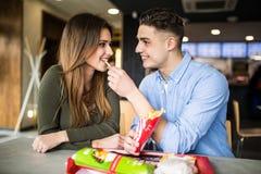 Det lyckliga caucasian paret som äter fransman, steker i snabbmat och har gyckel royaltyfri fotografi