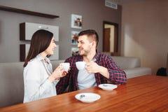 Det lyckliga förälskelseparet dricker kaffe på trätabellen arkivbilder