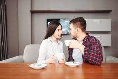 Det lyckliga förälskelseparet dricker kaffe på trätabellen royaltyfri fotografi