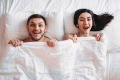 Det lyckliga förälskelseparet ligger på stor vit säng, bästa sikt fotografering för bildbyråer