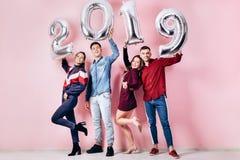 Det lyckliga företaget av två flickor och två iklädda stilfulla kläder för grabbar rymmer ballonger i formen av nummer 2019 arkivfoto