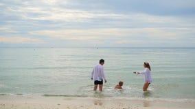 Det lyckliga familjinnehavet räcker spring längs kusten Till inkört vattnet som skapar färgstänk arkivfilmer