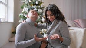 Det lyckliga ferie-, man- och kvinnalåset snöar med händer i rumsammanträde på golvet nära träd för nytt år stock video