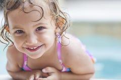 Det lyckliga flickabarnet behandla som ett barn i simbassäng Royaltyfri Fotografi