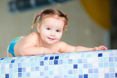 Det lyckliga flickabarnet behandla som ett barn i simbassäng Arkivfoto
