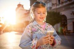 Det lyckliga flickabarnet lyssnar till musiken från hennes smartphone Arkivbilder