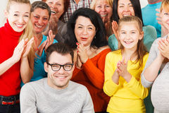 Det lyckliga folket applåderar deras händer. royaltyfria bilder