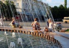 Det lyckliga folket går nära springbrunnen på en varm sommardag royaltyfria foton