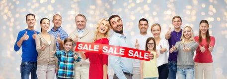 Det lyckliga folket med försäljning undertecknar upp visningtummar Royaltyfria Bilder