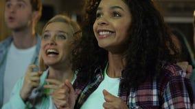 Det lyckliga folket som hurrar för den favorit- segern för sportlaget, afton i bar, kopplar av stock video