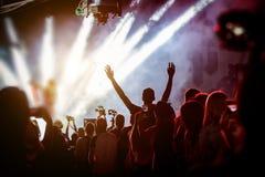 Det lyckliga folket som tycker om, vaggar konsert, lyftta upp händer och att applådera av nöje royaltyfri foto