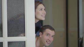 Det lyckliga gifta paret kontrollerar ett nyligen inhandlad hem eller lägenhet Le flickan och mannen som kikar ut ur dörren lager videofilmer