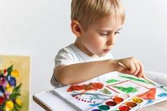 Det lyckliga gladlynta barnet drar målarfärger i ett album, genom att använda en variationsnolla fotografering för bildbyråer