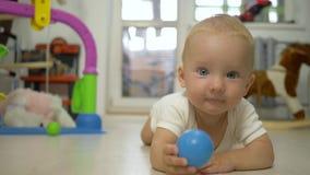 Det lyckliga gulliga lilla barnet med leksaken i händer ser kameran och kryper framåt närbild inomhus stock video
