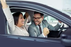 Det lyckliga härliga paret väljer en ny bil på återförsäljaren royaltyfria foton