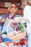 Det lyckliga höga bondeanseendet bak stannar och att sälja organiska grönsaker i en marknadsplats royaltyfria bilder