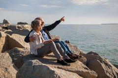Det lyckliga höga paret som sitter på, vaggar vid havet royaltyfri bild