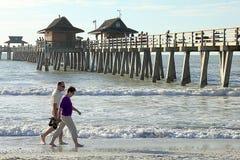 Det lyckliga höga paret tycker om en romantisk promenad på stranden arkivbilder