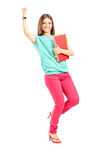 Det lyckliga innehavet för den kvinnliga studenten bokar och göra en gest lycka Royaltyfri Fotografi