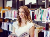 Det lyckliga innehavet för den kvinnliga studenten bokar på arkivet arkivfoto