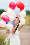 Det lyckliga innehavet för den unga kvinnan i färgrika latexballonger för händer överträffar Royaltyfri Fotografi