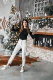 Det lyckliga innehavet för leendeflickakvinnan räcker det nya årets ballonger i dekorerat rum med julgranen och spisen nummer arkivfoton