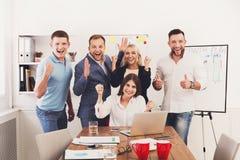 Det lyckliga laget för affärsfolk firar framgång i kontoret Arkivbild