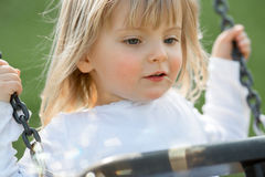 Det lyckliga le barnet behandla som ett barn utomhus- spela för caucasian blont verkligt folkflickaslut på gunga arkivbild