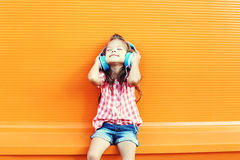 Det lyckliga le barnet tycker om lyssnar till musik i hörlurar över apelsinen royaltyfri foto