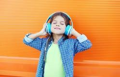 Det lyckliga le barnet tycker om lyssnar till musik i hörlurar över den färgrika apelsinen royaltyfri fotografi