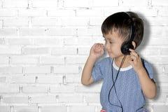 Det lyckliga le barnet tycker om lyssnar till musik i hörlurar royaltyfri bild