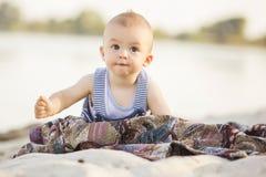 Det lyckliga le gulliga lilla spädbarnet behandla som ett barn på ett near vatten för kust Royaltyfria Bilder