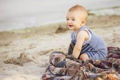 Det lyckliga le gulliga lilla spädbarnet behandla som ett barn på ett near vatten I för kust Royaltyfri Fotografi