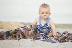 Det lyckliga le gulliga lilla spädbarnet behandla som ett barn på ett near vatten I för kust Arkivfoton