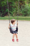 Det lyckliga le pyslilla barnet i tshirt och jeans kortsluter på gunga på trädgårdlekplats utanför Arkivbilder