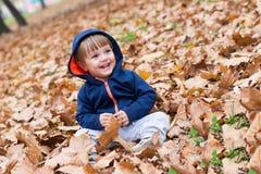 Det lyckliga lilla barnet, behandla som ett barn pojken som skrattar och spelar i höst Arkivbild