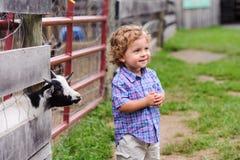 Det lyckliga lilla barnet på lantgården med behandla som ett barn geten Royaltyfri Foto
