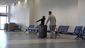 Det lyckliga lilla barnet sitter på stort bagage och dansen, faderpushresväska lager videofilmer