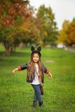 Det lyckliga lilla barnet som poserar för kameran, behandla som ett barn flickan som skrattar, och spela i hösten på naturen gå u Fotografering för Bildbyråer