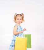 Det lyckliga liten flickainnehav upp shopping hänger lös bags flickan som rymmer little shopping Royaltyfria Foton