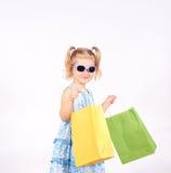 Det lyckliga liten flickainnehav upp shopping hänger lös bags flickan som rymmer little shopping Arkivbilder