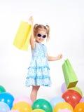 Det lyckliga liten flickainnehav upp shopping hänger lös bags flickan som rymmer little shopping Arkivfoto