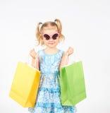 Det lyckliga liten flickainnehav upp shopping hänger lös bags flickan som rymmer little shopping Royaltyfria Bilder