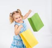 Det lyckliga liten flickainnehav upp shopping hänger lös bags flickan som rymmer little shopping Royaltyfri Bild