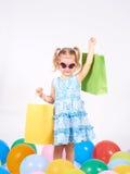 Det lyckliga liten flickainnehav upp shopping hänger lös bags flickan som rymmer little shopping Royaltyfri Foto